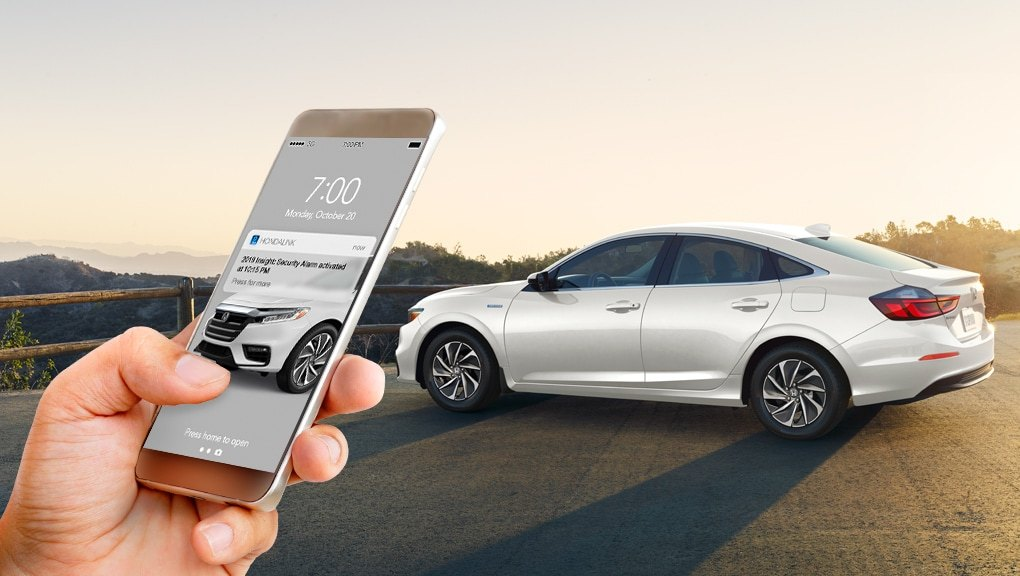 a hand holding a smartphone with a Honda Insight in the background