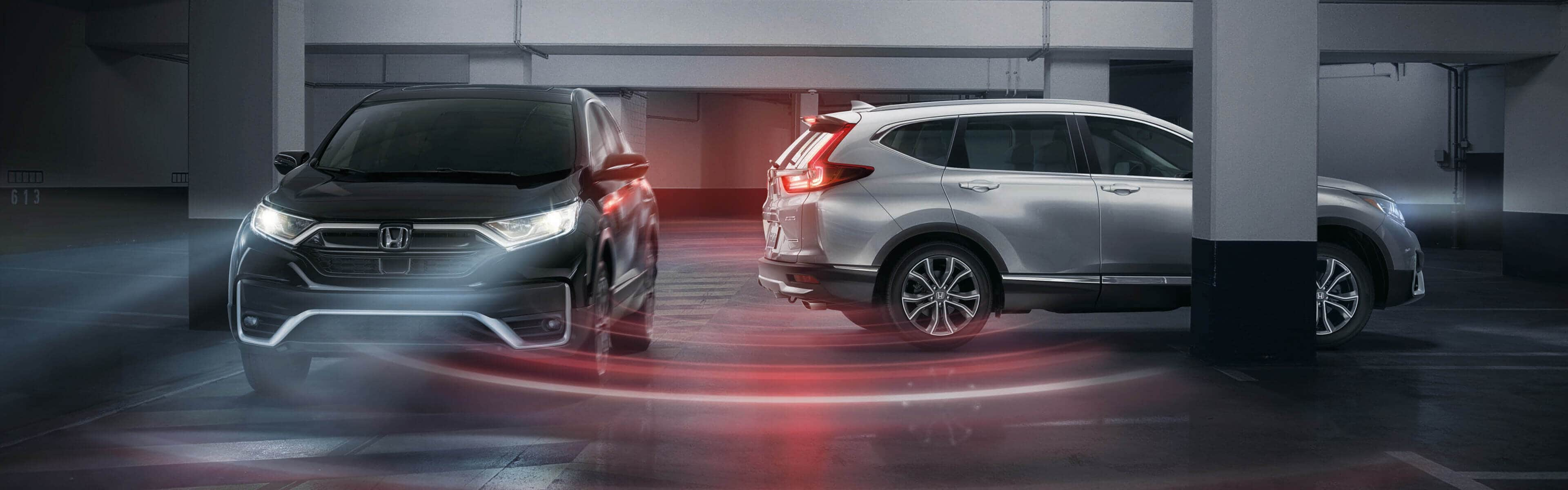 two Honda CR-Vs in a parking lot, avoiding a collision thanks to an animated expression of Honda Sensing technologies